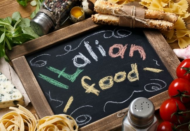 Themed Family Dinner Ideas - Italian Night - Chalkboard with Italian Food written on it, fresh pasta, cheese wedges, fresh parsley, cherry tomatoes and shakers of spices