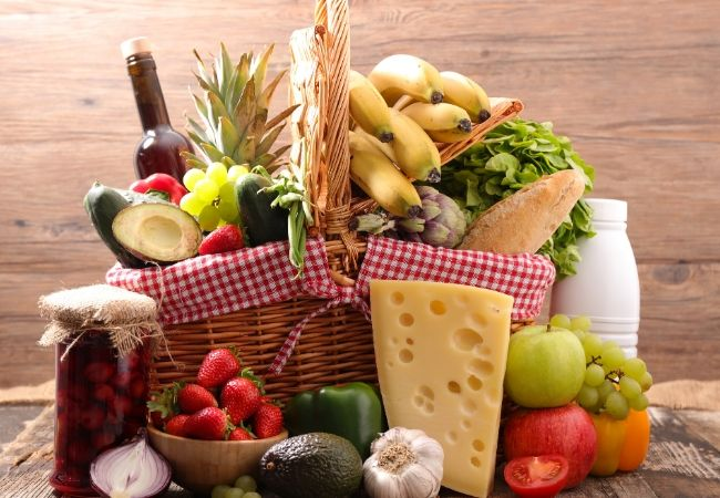 Themed Family Dinner Nights - Chopped! A spin-off. - Basket with red and white checkered liner filled with bananas, wine, pineapple, artichokes, Swiss cheese, apples, grapes, avocados. On the side of the basket is a bowl of strawberries, garlic, pepper, jar of olives.