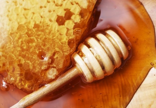 Raw honey comb on a wooden background