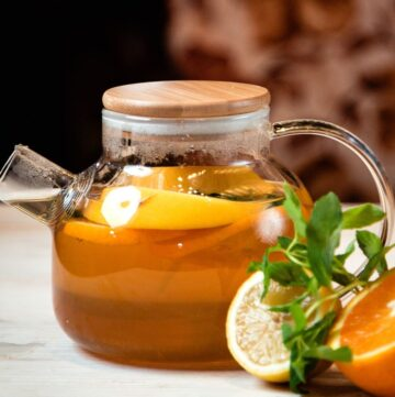 Cold Remedy Tea Recipe in a clear teapot with slices of oranges and lemons