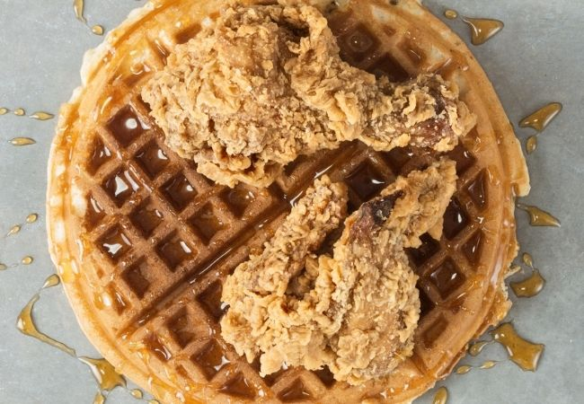 Large round waffle with two pieces of Fried Chicken on Top and Maple Syrup