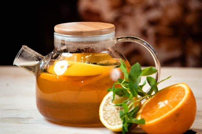 Clear teapot with cold remedy tea with orange and lemon slices. Sliced orange and lemon on the side of the teapot.