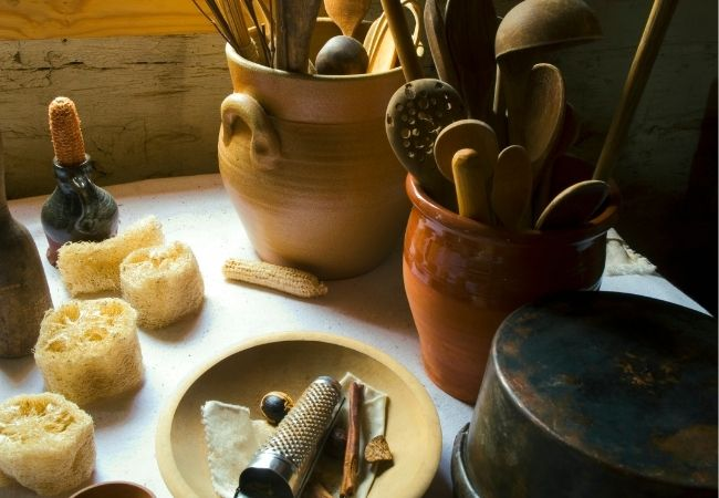 Table with antique pottery pots with vintage utensils and wooden bowl