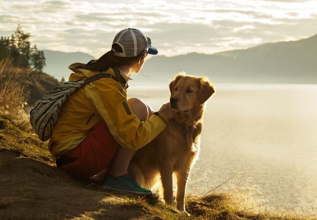 Woman in hiking attire with backpack and Golden Retriever in front of a lake