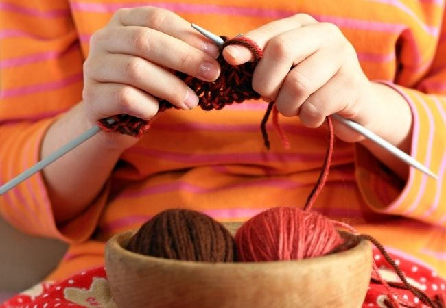 Close-up of woman's hands knitting with two balls of yarn in a wooden bowl in front of her. She is wearing an orange shirt and the yarn are burnt orange and brown
