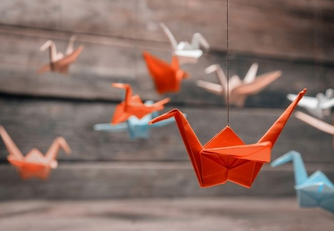 Origami birds hanging from wire in front of rustic boards