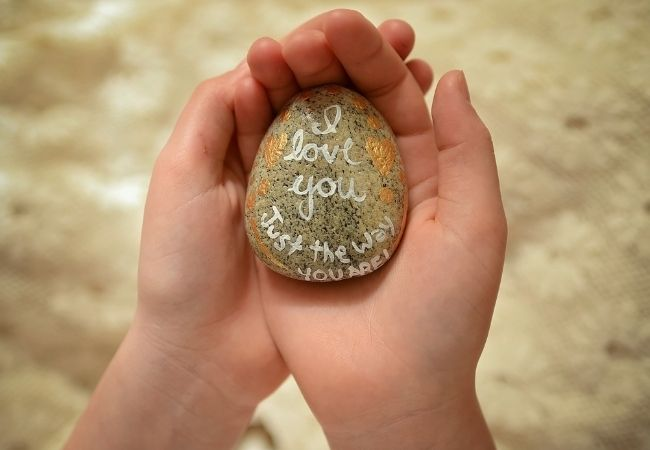 Young hands holding a painted rock that says I love You
