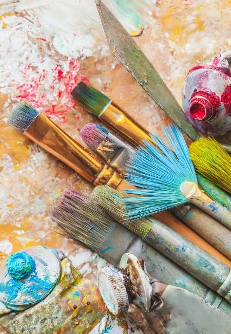 Paint brushes with paint on them on top of a paint splattered paper