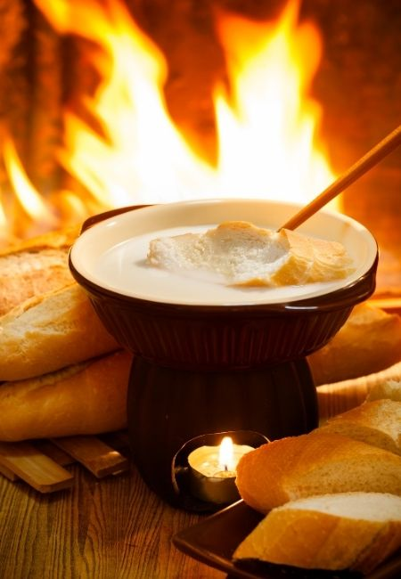 Cheese Fondue Dippers - cheese fondue pot in front of a fireplace with loaves of bread and a fondue fork with a piece of bread being dipped in the cheese fondue
