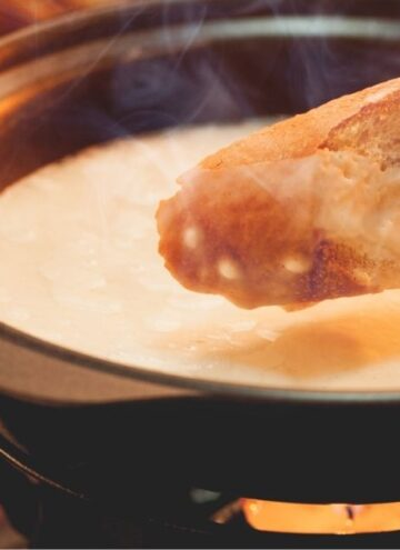 Piece of baguette being dipped in cheese fondue one of The Best Cheese Fondue Dippers