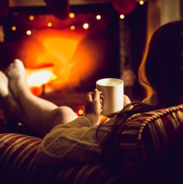 31 Hygge Home Decor Ideas for 2021 - Woman in front of a fireplace with her back towards the camera with mug of tea in her hand