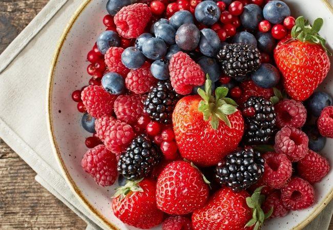 Chocolate Fondue Recipe Ideas - Berries. Fresh strawberries, blackberries, raspberries, and blueberries are on a white plate.