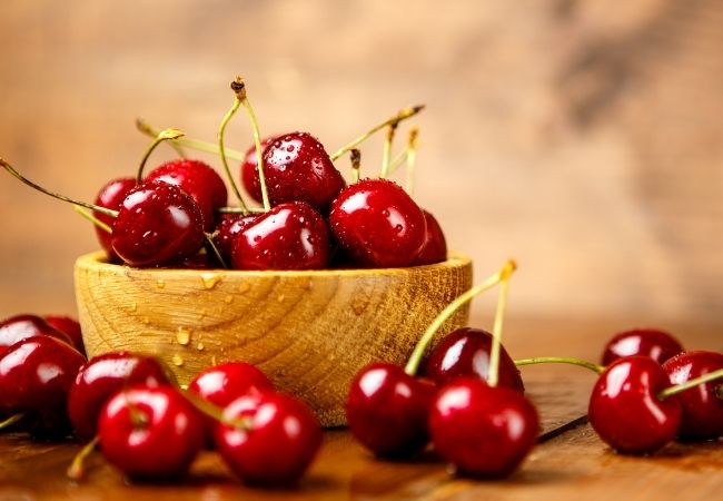 Chocolate Fondue Recipe Ideas - Fresh Cherries in a wooden bowl on a wooden surface