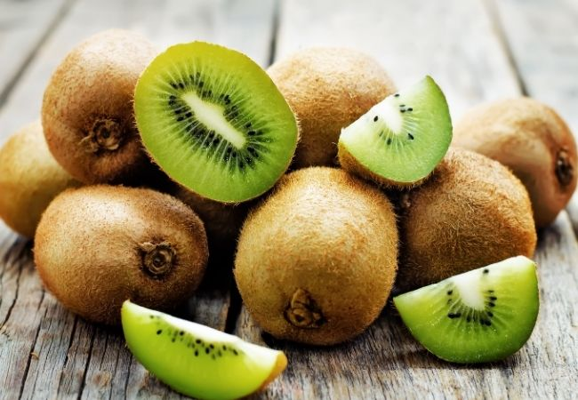 Chocolate Fondue Ideas - Kiwi Fruit cut up on a rustic surface with whole kiwi