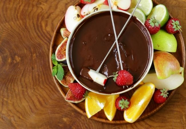 Best Chocolate Fondue Recipe with Fruit Slices - overhead photo of chocolate fondue with two fondue forks with fruit resting on top. Slices of fresh fruit are on a plate holding the fondue pot.