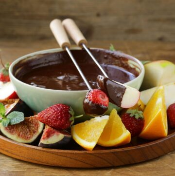 Easy Creamy Chocolate Fondue Recipe in a fondue pot surrounded by fresh fruit.