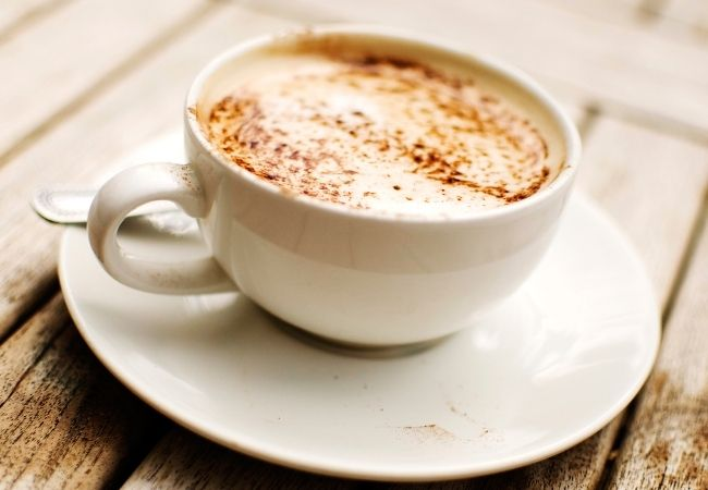Latte in a white cup and saucer sprinkled with cinnamon