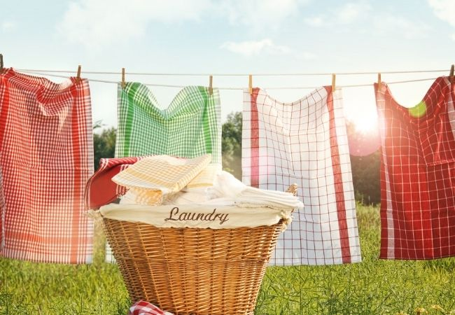 Save money by drying laundry on a clothes line with wicker basket in front