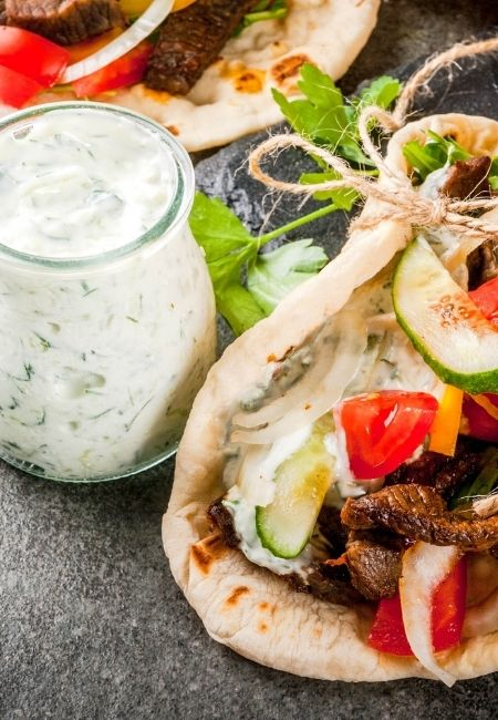 Homemade tzatziki sauce in a small clear glass bottle next to a gyro with tzatziki sauce