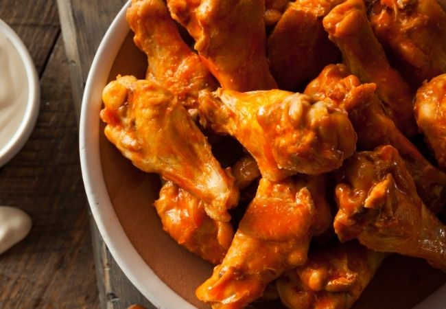 Homemade buffalo sauce on chicken wings on a plate