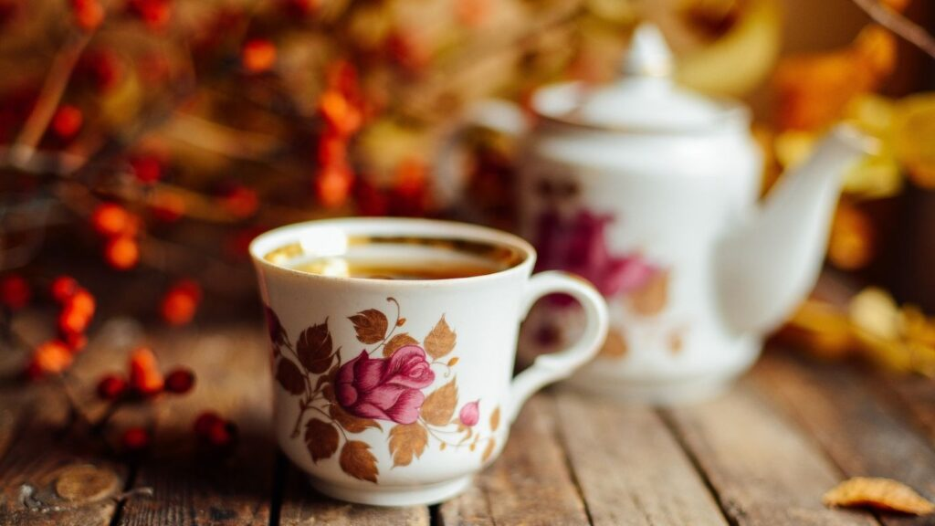 31 Fall Hygge Traditions & Ideas - Teapot and tea cup and saucer with fall foliage.