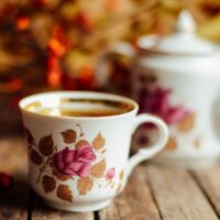 31 Fall Hygge Traditions & Ideas - Tea cup and teapot with fall foliage in the background.