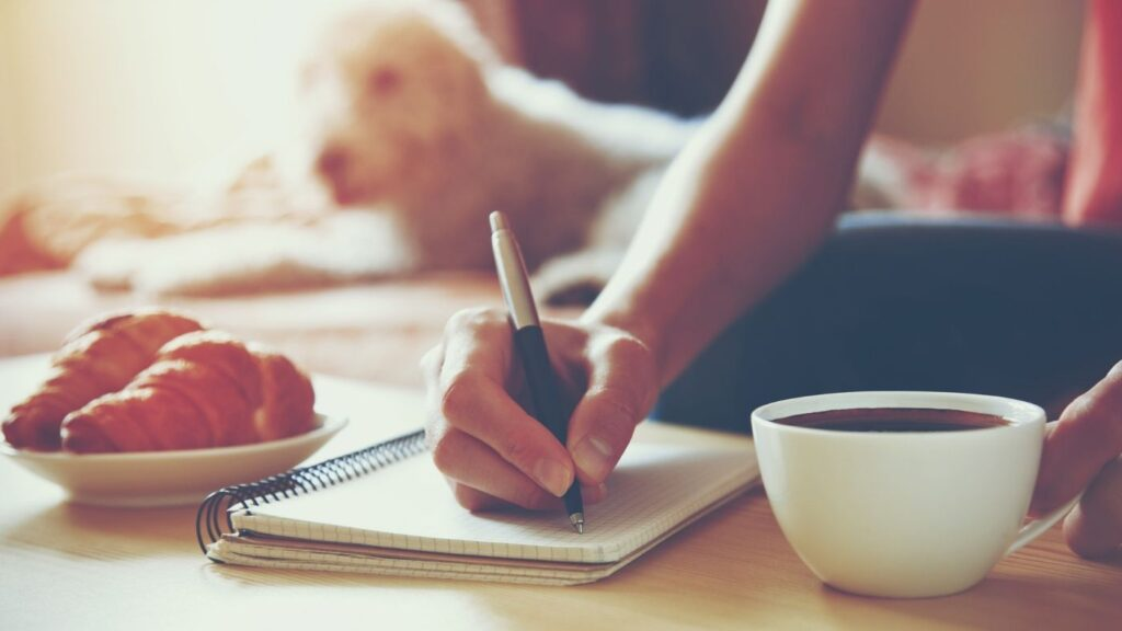 Best Journal Ideas - Woman journaling with coffee and croissants.