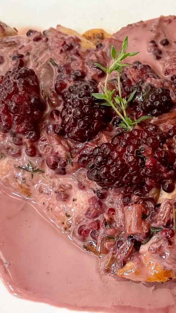 Creamy Blackberry Chicken Recipe on a white plate with a fresh sprig of thyme.