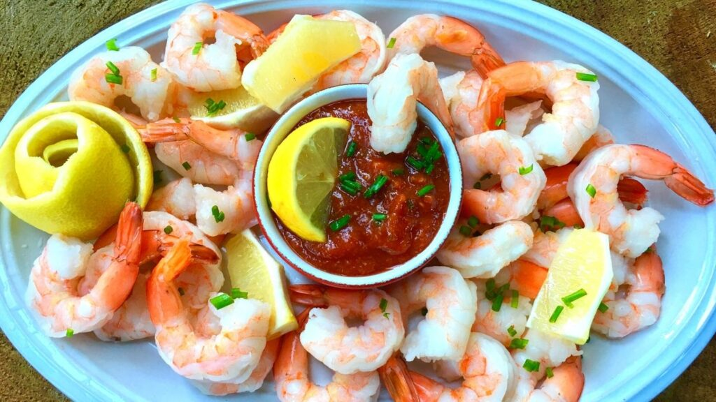 Homemade Cocktail Sauce Recipe in a small bowl, surrounded by shrimp and lemon wedges.