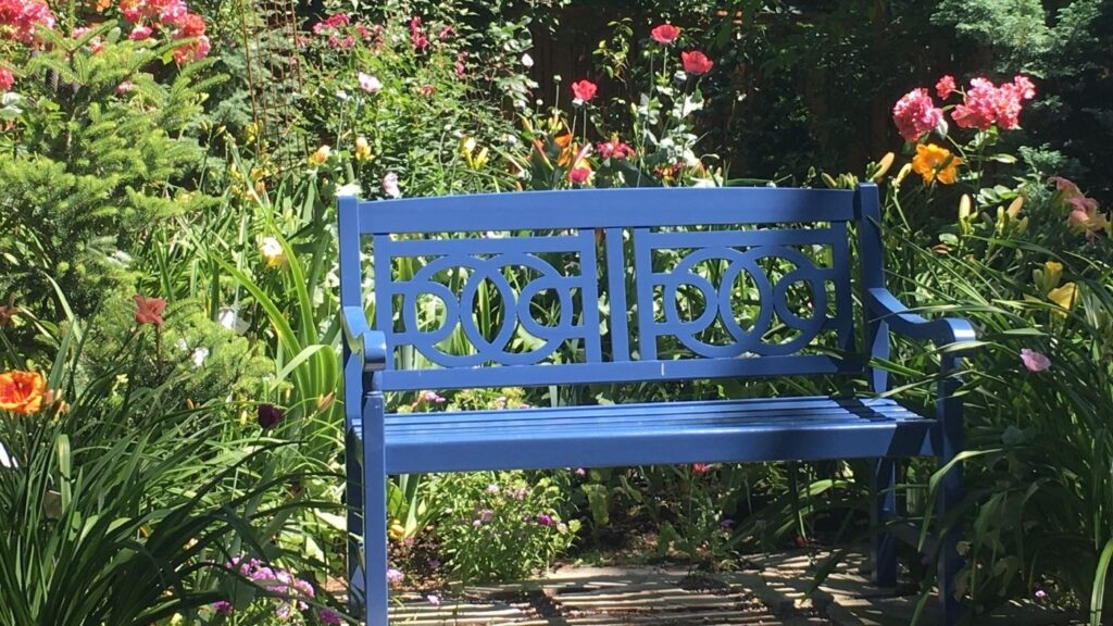 How to Add Hygge to Your Garden - Gardening Bench Surrounded by Flowers