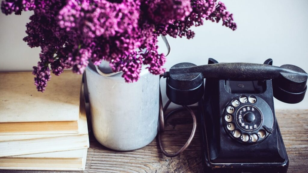 How to Hygge at Work - Vintage phone with vase of flowers and stack of books