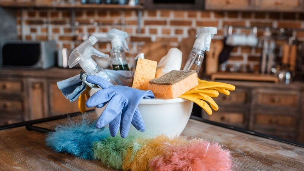 How to Add Hygge to Your Cleaning - Cleaning supplies in a bowl with a Duster in a Rustic Kitchen