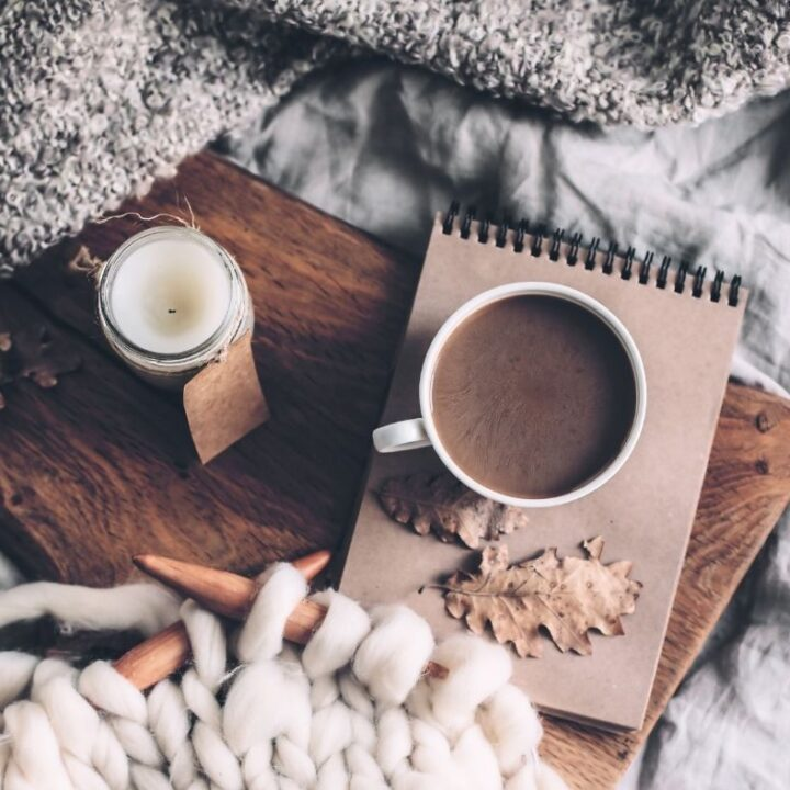 Hygge Bedtime Rituals to Try Tonight - Gray Bedding with Wooden tray, coffee, sketch pad, knitting, candle