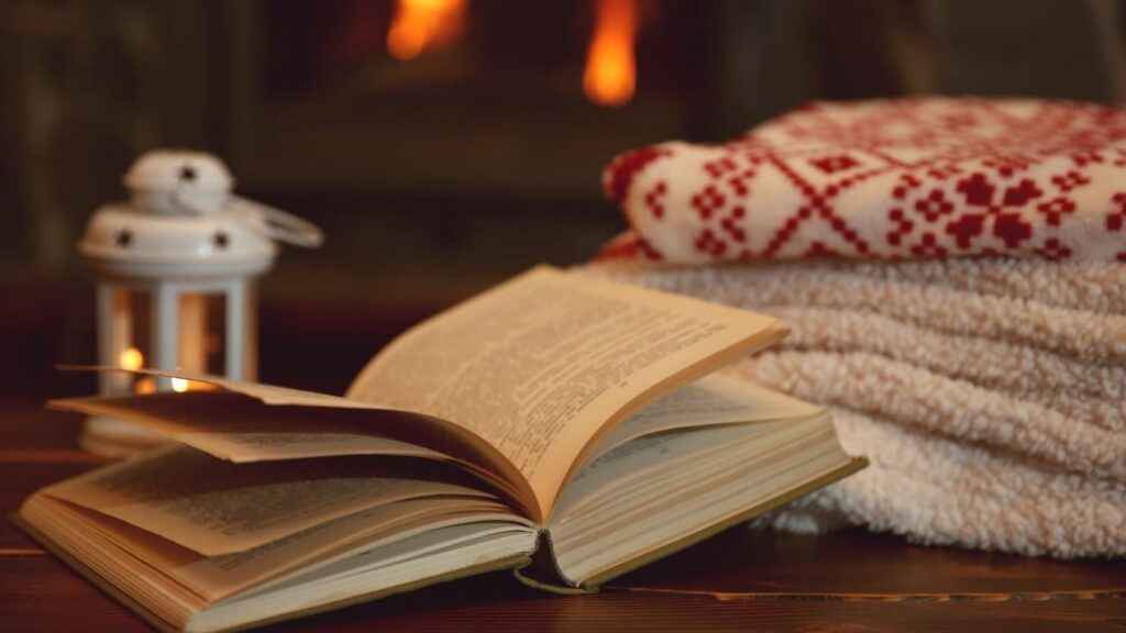 Hygge Book Ideas - Lantern with open book and pile of sweaters
