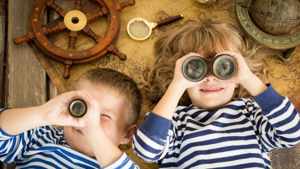 Hygge Children - Two children laying on their backs with binoculars on top of an old map and globe nearby