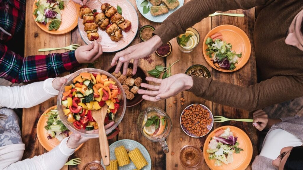 Hygge Gathering of Friends - overhead photo of a table and hands and food at meal time.