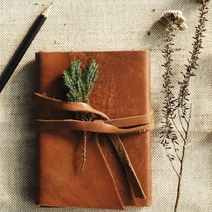 Hygge Journal Prompts - leather journal with pencil and flowers