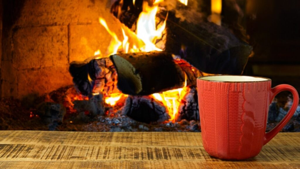 Hygge Quotes to Soothe Your Soul - Orange mug on a table in front of a fireplace.