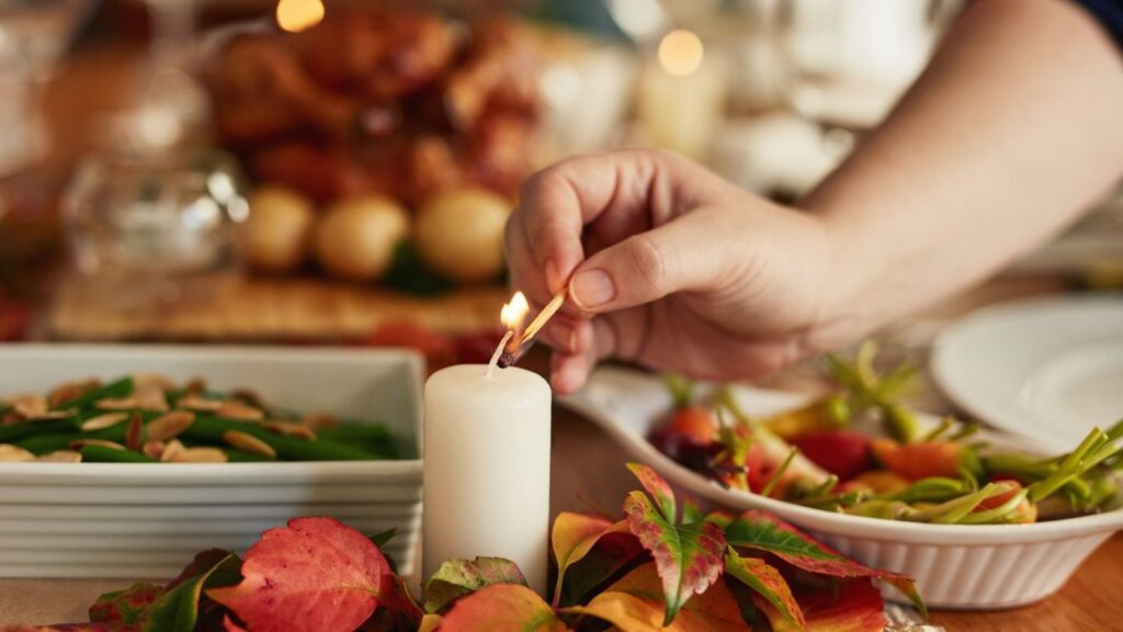 Intimate Family Dinners - Table with food and candle with hand lighting the candle