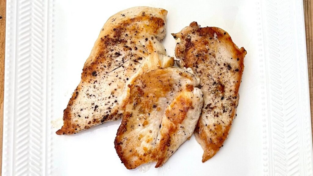 Pan seared chicken breasts on a white plate with salt and pepper.