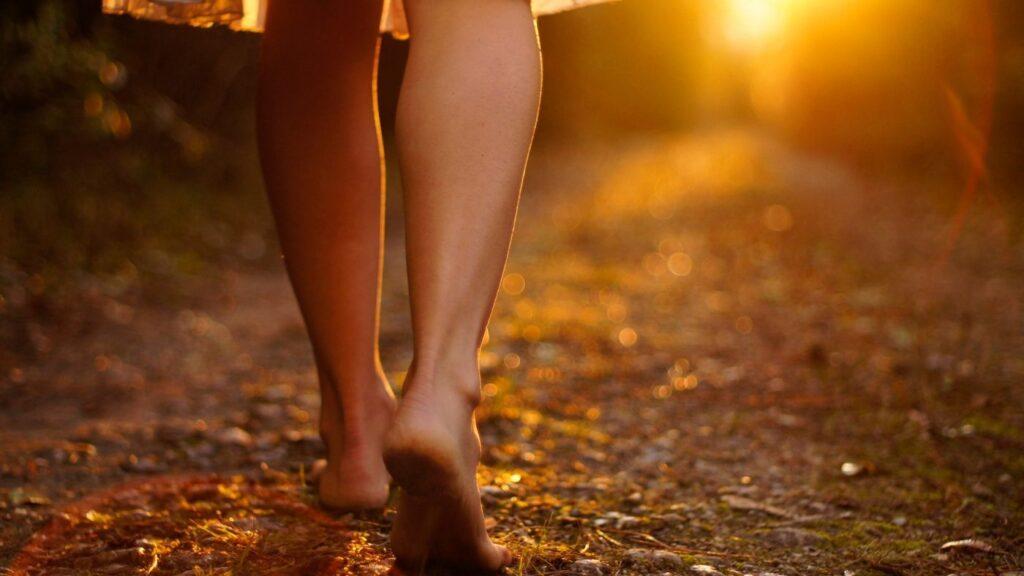 Bottom half of woman barefoot walking in nature