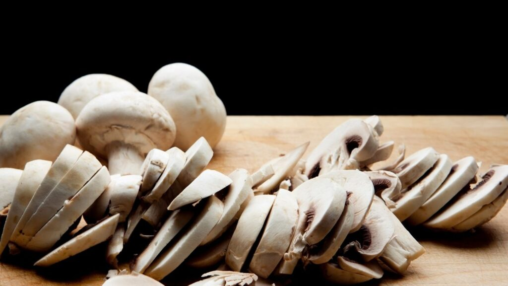 White or button mushrooms sliced on a cutting board.