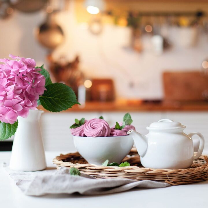 21 Secrets to a Tidy Home - wicker tray with white teapot and bowl of treats and a vase of flowers in front of kitchen