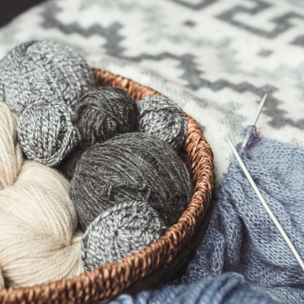 31 Hygge Hobbies to Try - Wicker Basket with gray and cream balls of yarn