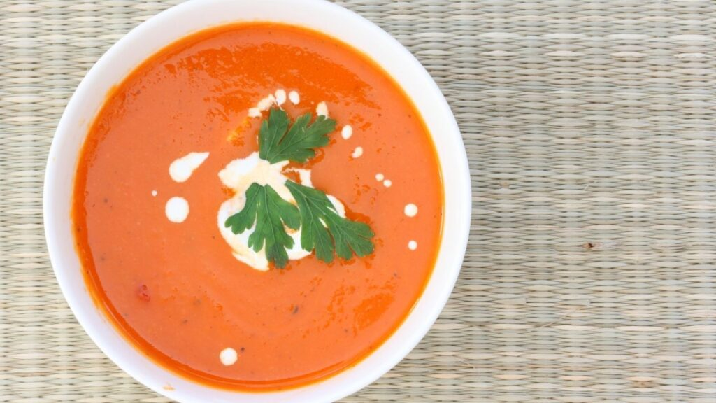 Best Creamy Tomato Soup Recipe - overhead view with sour cream and parsley in a white bowl