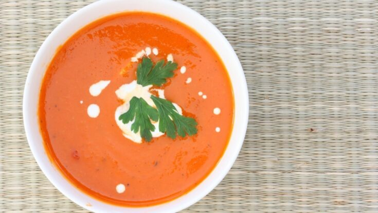 Homemade Creamy Tomato Soup Recipe overhead photo with sour cream and parsley in a white bowl