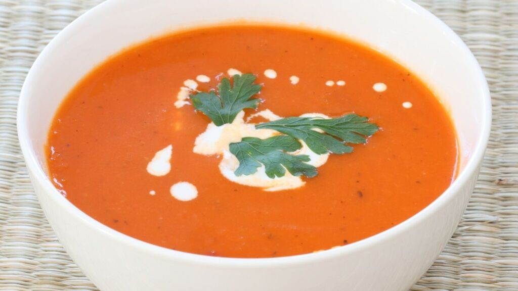 Best Creamy Tomato Soup Recipe in a white bowl with sour cream and parsley