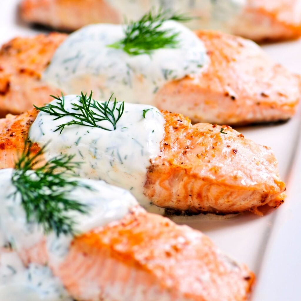 Cooked pieces of salmon with dill sauce on top and sprigs of fresh dill