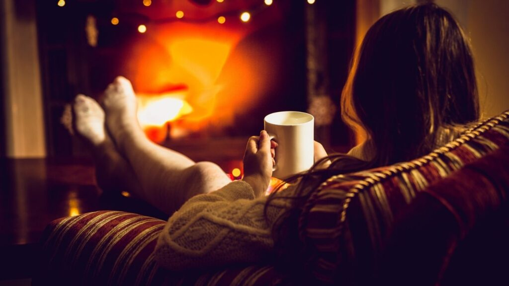 How to Create a Hygge Home - Woman sitting in front of a fireplace with her back to the camera cozy chair drinking tea.