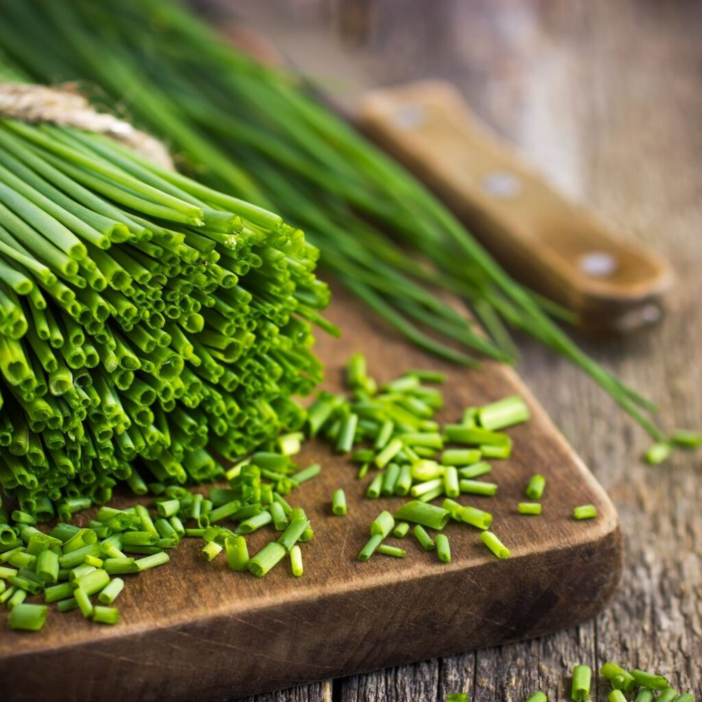 How to Grow Chives - Rustic cutting board with chives being chopped